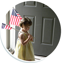 Girl with two American Flags walking through a doorway