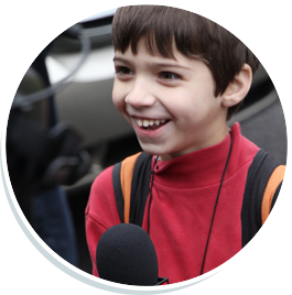 Boy smilling in front of a large microphone